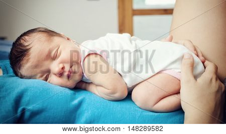 Portrait of sleeping newborn baby girl with mom.