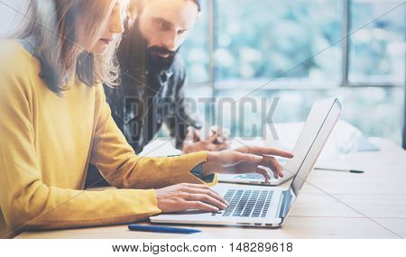 Closeup Two Modern Coworkers Discussing Together During Working Process.Young Business People Meeting Concept.Discussion Startup Project Office.Hipsters Work Laptop Wood Desk Table.Blurred