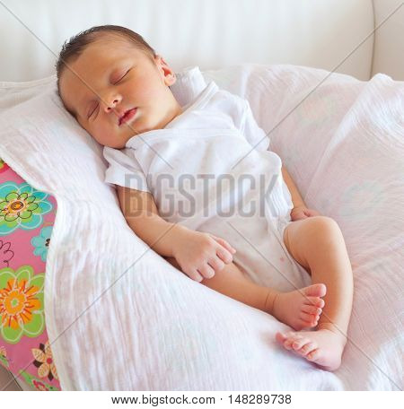 Portrait of sleeping newborn baby girl on white sofa
