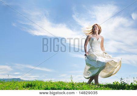 feliz novia hermosa joven después de evento de ceremonia de boda tener diversión al aire libre en el Prado al atardecer