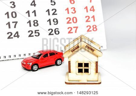 Wooden house and toy car on a calendar background