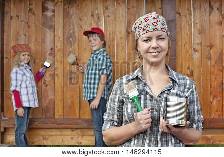 Kids helping their mother painting the wood shed - woman in foreground