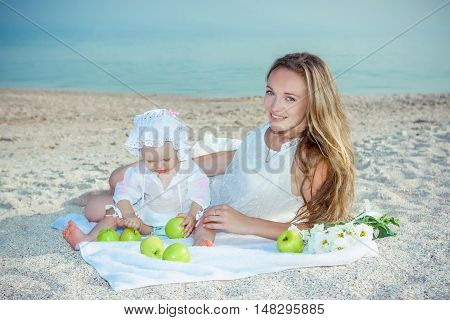 Happy family. Mother and her daughter having fun on the beach. With green apples. Positive human emotions feelings.