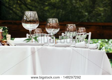 Table for guests on the veranda, white tablecloths and napkins in the background of green Park.
