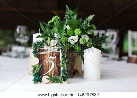 The decor at the wedding. Beautifully decorated table, with the decor. The sign in rustic style, plates and cups.
