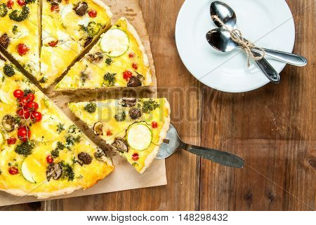 Freshly baked homemade pie quiche lorraine on a wooden table, top view, copy space