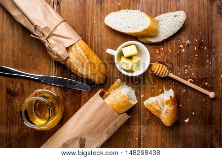 Breakfast in traditional style - white baguette with butter and honey. On a wooden table, top view, copy space