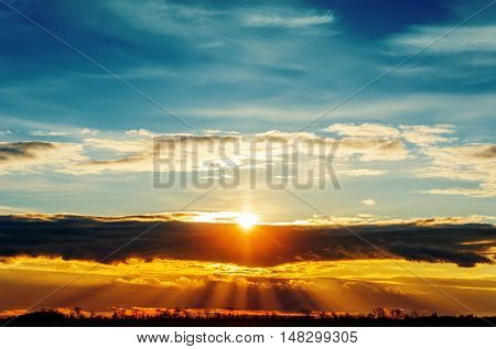 sun over dark clouds in sunset time