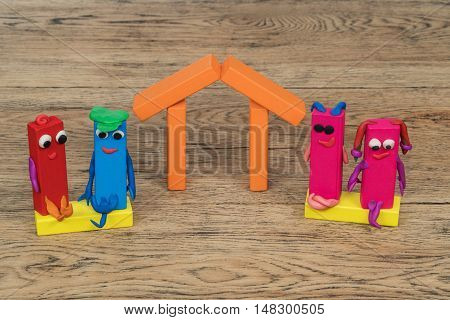 House made of wooden blocks and four people families from plasticine located on an old wood table