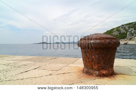 Rusty metal mooring bolard for big ship.