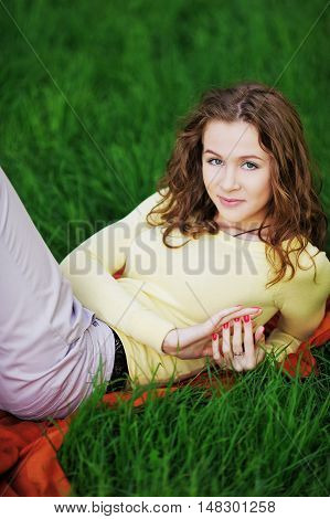 Elegant gray-eyed girl in a yellow jersey charming smiles and stares at you resting on the green grass