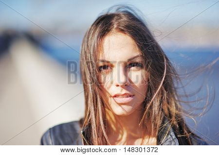 Portrait of a young cute brunette with tousled hair in the wind on a clear sunny day close-up