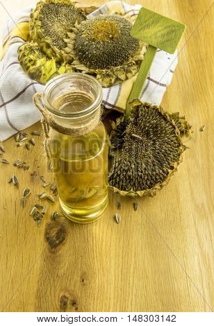 Sunflower plants and a bottle with oil - Glass bottle with sunflower oil and a basket with sunflower plants on a wooden table