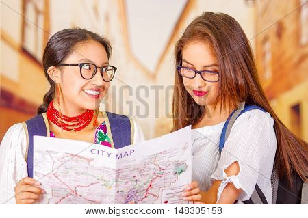 Two beautiful young women posing for camera, one wearing traditional andean clothing, the other in casual clothes, holding city map between them interacting, both smiling, park background.