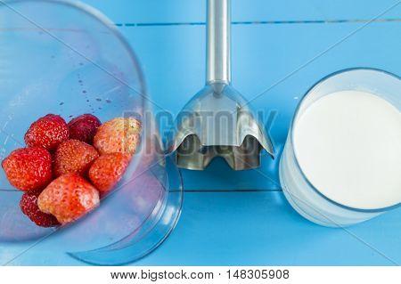 Ingridient for strawberry milkshake - strawberries in glass, milk and blender