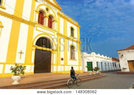 MOMPOX COLOMBIA - MAY 28: Woman rides a bicycle past the cathedral in Mompox Colombia on May 28 2016