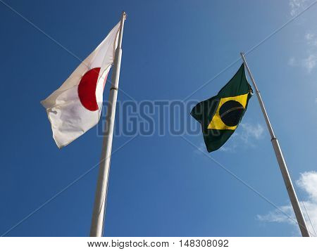 Flags of Japan and Brazil waving wind sky