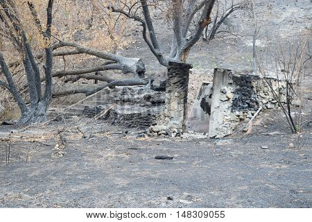 Foundation of a burnt home surrounded by ash taken after a wildfire in Southern California