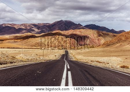 Old highway goes to montains and cloudy sky
