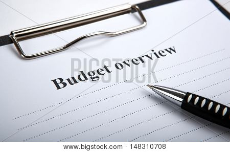 document with title budget overview and pen close up