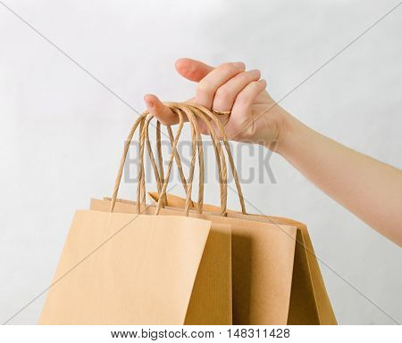 a brown kraft bag in hand on white background