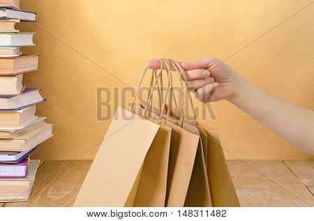 a brown kraft bag in hand on golden background