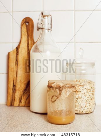 real comfort wooden kitchen with breakfast ingredients close up in glass, honey, oatmeal, milk, muesli food