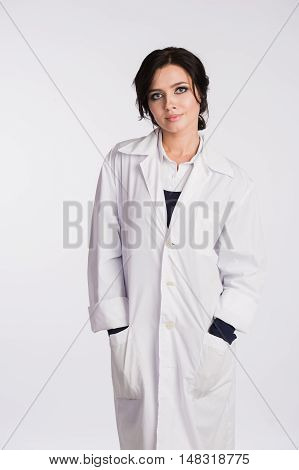 Smiling medical doctor woman with hands in pockets of robe looking at camera isolated on white.