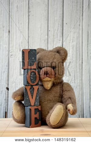 Antique brown teddy bear sitting with Love stones against withe wood slats