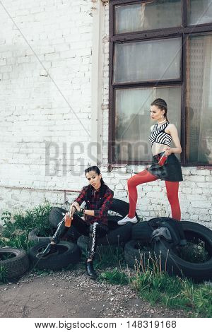 Two Young Girls Sitting On Tires On Sunny Day