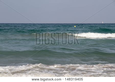 view of the sea with waves in the foreground and a sailboat in the background on the right