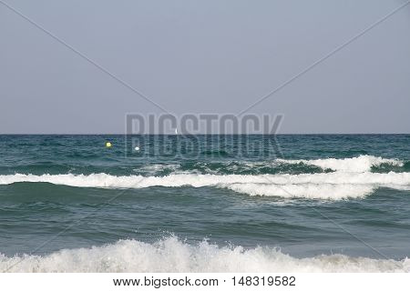 view of the sea with waves in the foreground and a sailboat in the background