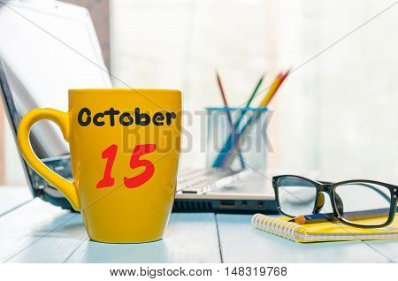 October 15th. Day 15 of month, hot coffee cup with calendar on accauntant workplace background. Autumn time. Empty space for text.