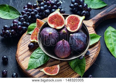 Fresh ripe figs and black grapes on wooden chopping board. Concept of freshness, healthy food, fresh fruits, summer market harvest and colors.