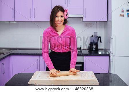 beautiful woman prepares pizza dough in the kitchen