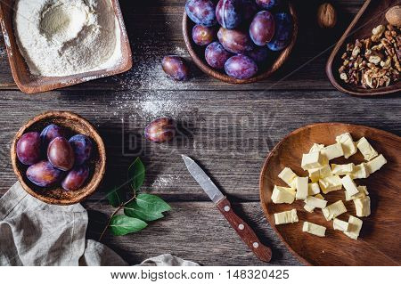 Ingredients for plum pie: fresh plums, walnuts, flour with sugar and chopped butter on rustic wooden table. Overhead view