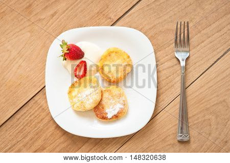 Breakfast of tasty round pancakes with cottage cheese with fragrant red ripe strawberries on a square white plate and coffee with milk cappuccino