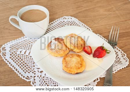 Breakfast of tasty round pancakes with cottage cheese with fragrant red ripe strawberries on a square white plate and coffee with milk cappuccino on wood desk.