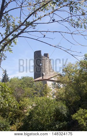 Antique Tower Made Of Stone Surrounded Of Trees In Lagrasse, France