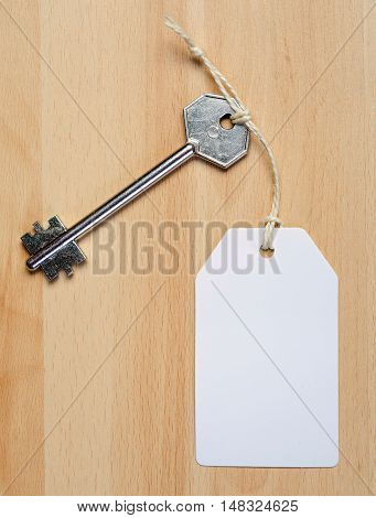 white paper tag attached to the metal silver key on the wooden background