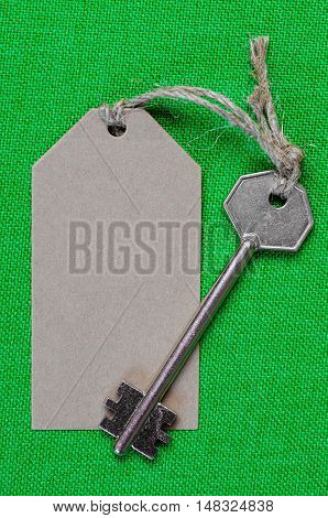 grey paper tag attached to the metal silver key on the green  fabric background