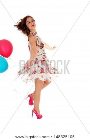 A gorgeous young woman dancing in a dress with balloons in her hand isolated for white background.