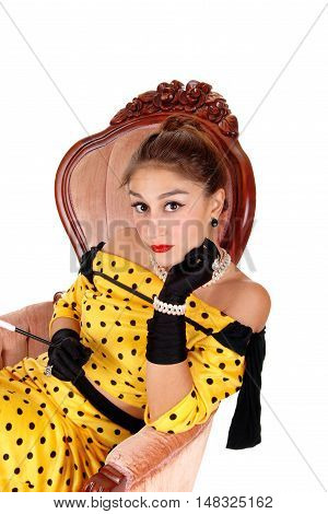 A gorgeous young woman sitting in a pink armchair in a yellow dress and wearing black cloves and jewellery isolated for white background.