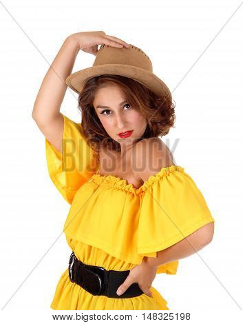 A beautiful young woman standing in a yellow blouse isolated for white background holding a cowboy hat on her head.