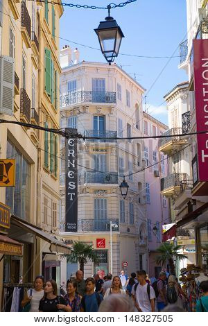 CANNES, FRANCE - 19 SEPTEMBER, 2016: Centre of the town view with restaurants, cafes and lots of walking people. Old city of Cannes colorful houses.