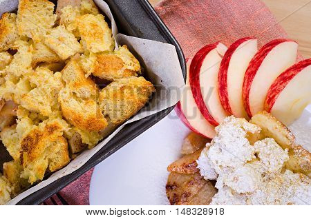 apple pie on a white plate decorated with raw apples on a wooden background