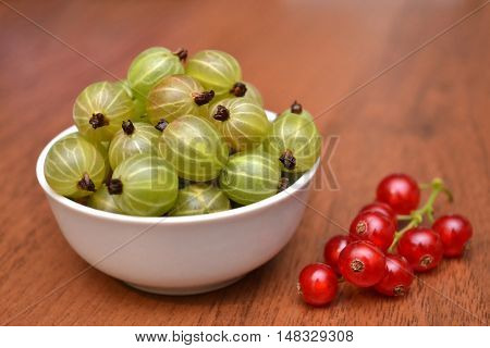 Gooseberry and red currant in the white plate on a wooden table
