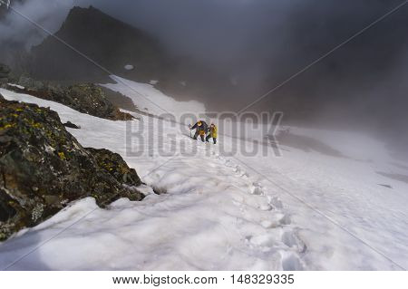 Two climbers in the mountains rise clouds