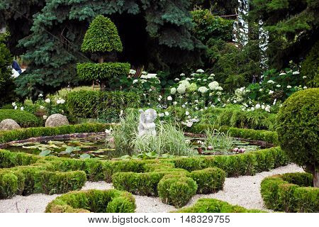 Background of garden design. Landscaping in park with pond, boy angel statue and lotus flowers