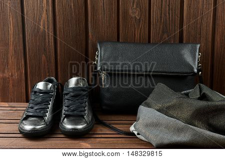 Leather Upper Metallic Womens Shoes, Scarf And Black Leather Bag On Brown Wooden Background.  Womens